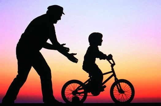 ребенок и дедушка учит его ездить на велосипеде